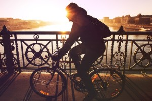 sunset image of person riding across a bridge on a bike