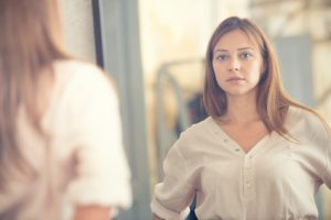 Young woman looking in the mirror with a serious but neutral expression